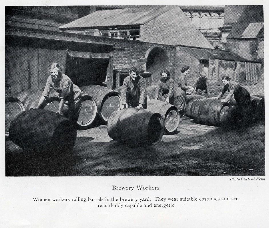 Photograph of women moving barrels.