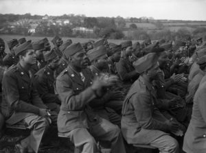 Black and white photograph showing group of seated Black soldiers clapping.