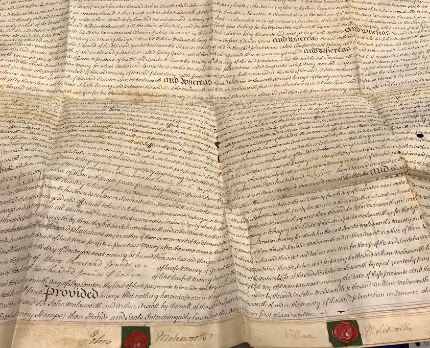 Photograph of a large handwritten document with two red wax seals at the bottom.