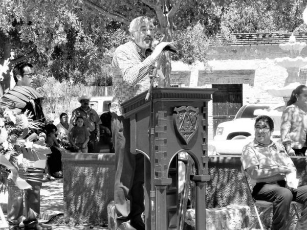 Black and white photo of male speaker at a podium outdoors.