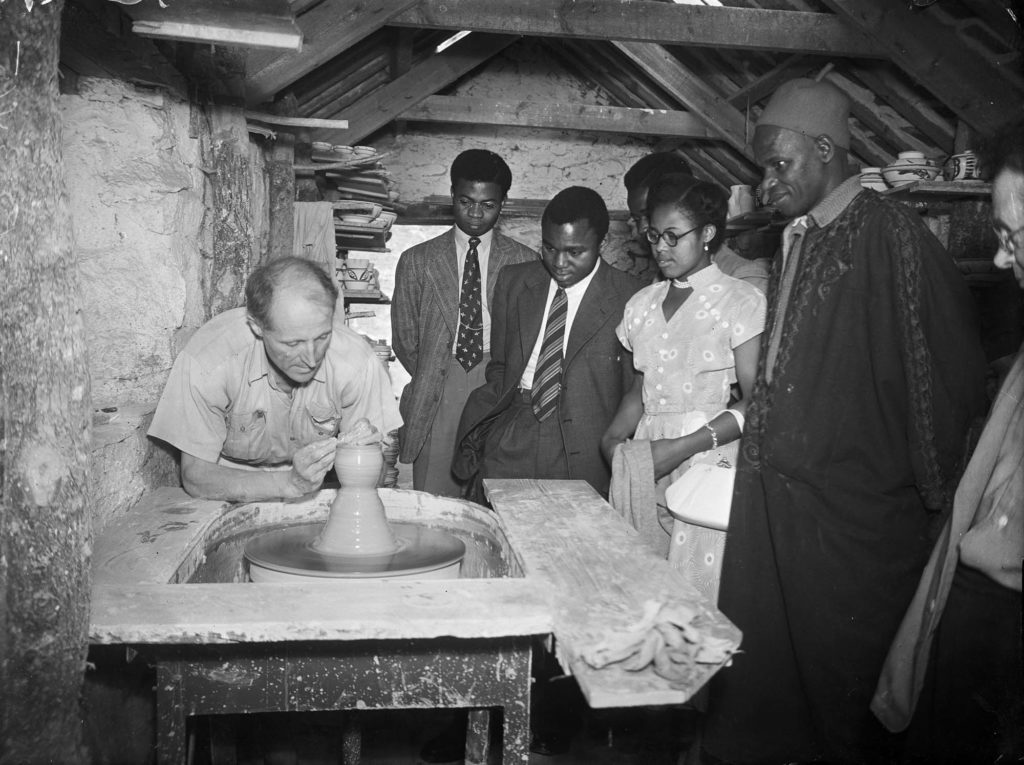 Black and white photo of a white man giving a pottery demonstration watched by a group of Black men and women.