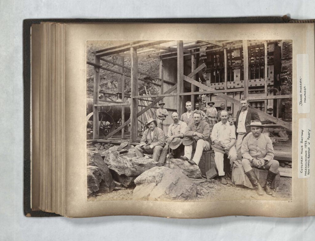Scan from a photo album showing a black and white photo of a group of people outdoors including Cecil Rhodes.