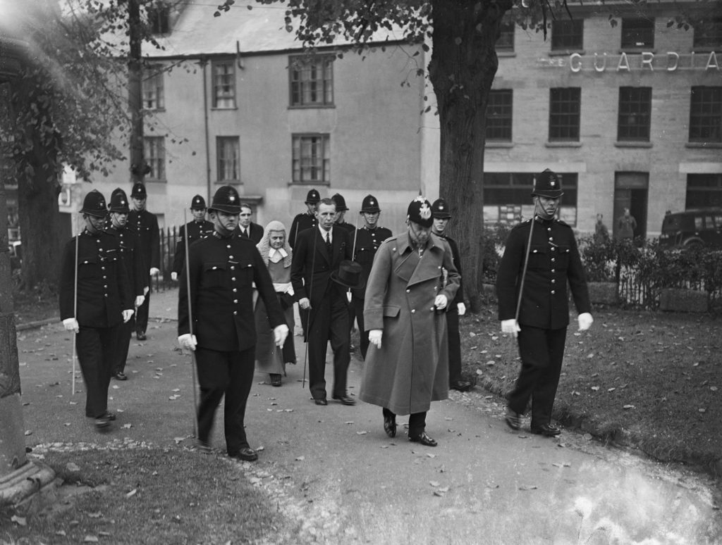 Photograph of a Judge and escort walking to court.