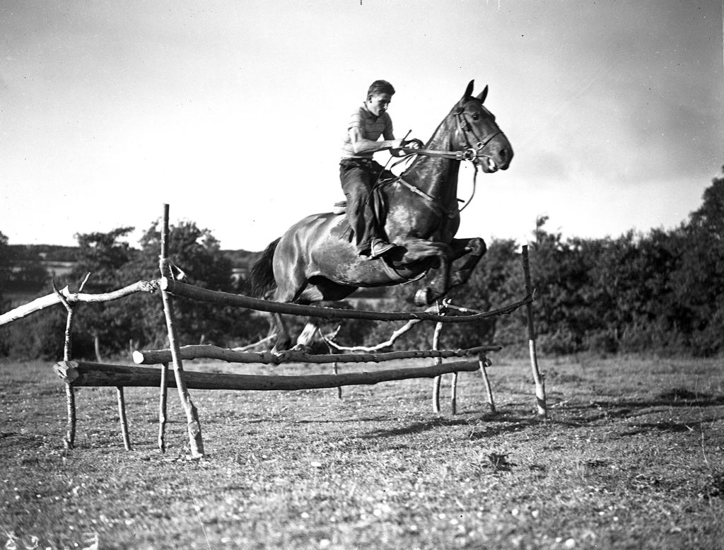 Photograph of a horse and rider clearing a jump.