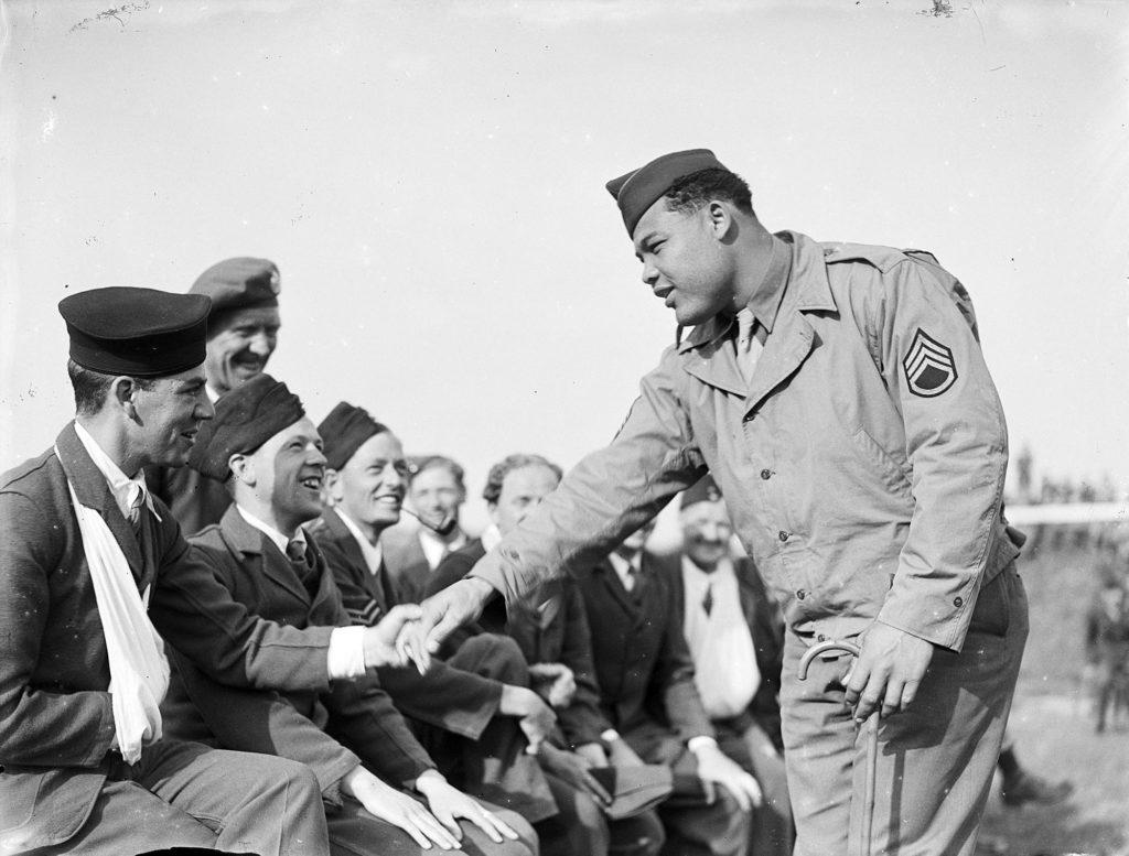 Photograph of boxer Joe Louis meeting troops.
