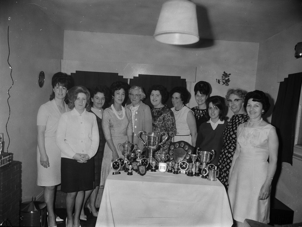 Photograph of a darts team and their trophies.