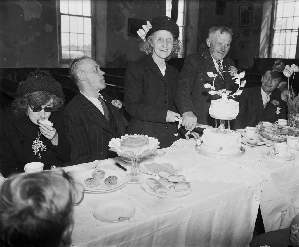 Photograph of a bride and groom cutting a wedding cake.