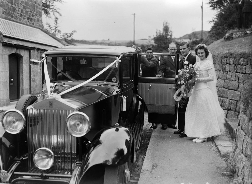 Photograph of a bride and groom standing beside a Rolls Royce