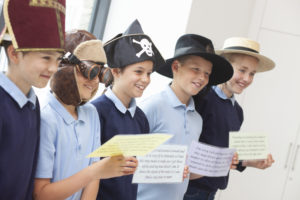 Colour photo of children wearing different hats and holding cards.