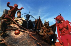 Colour photo showing actors in costumes and a dragon.