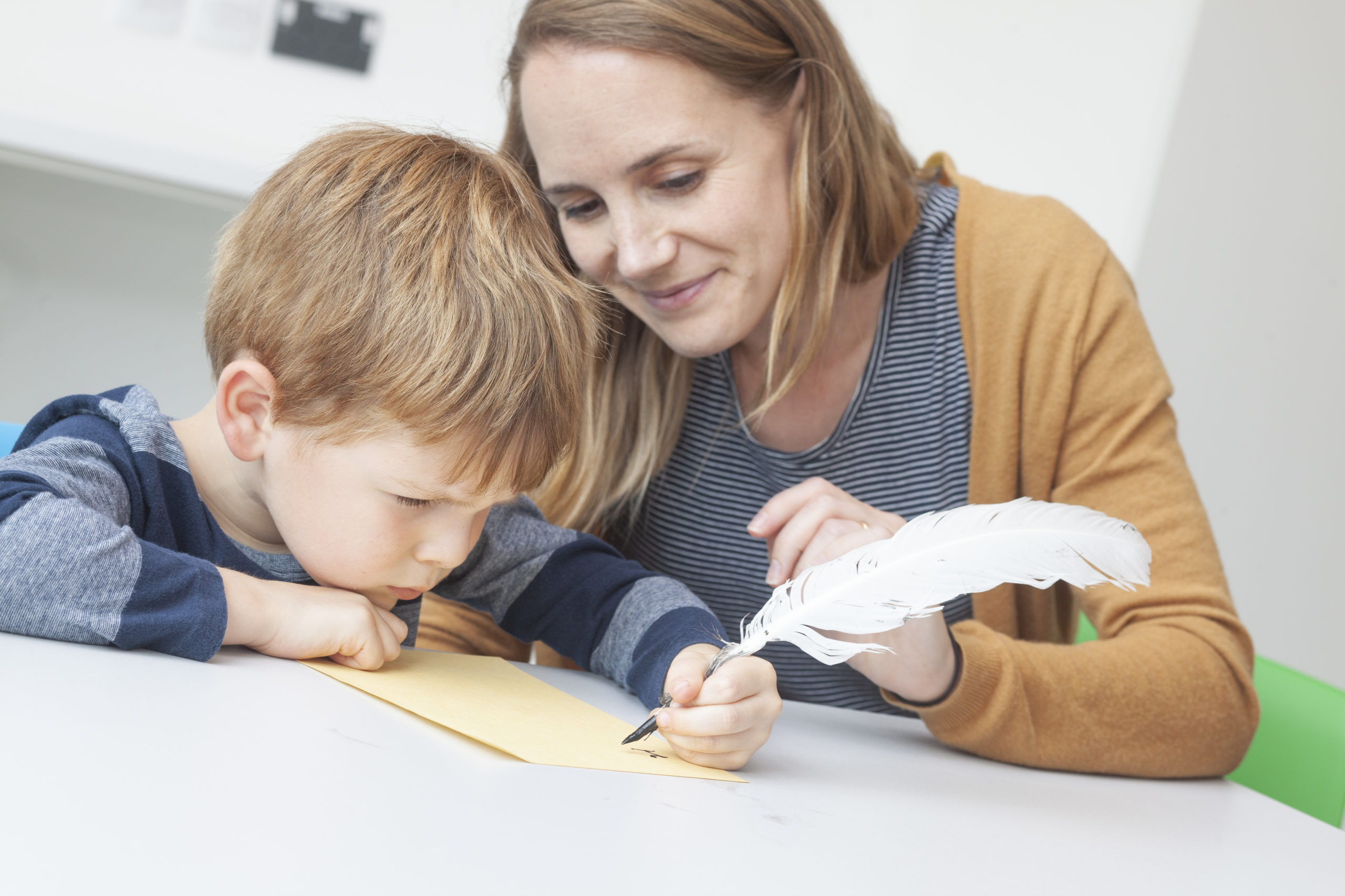 Modern colour photo of child with quill pen and mother watching.