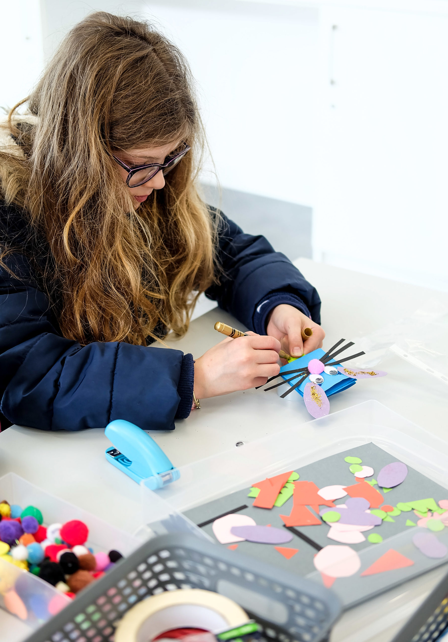 Modern colour photo of a girl creating crafts at a table, photo copyright Claire Chamberlain