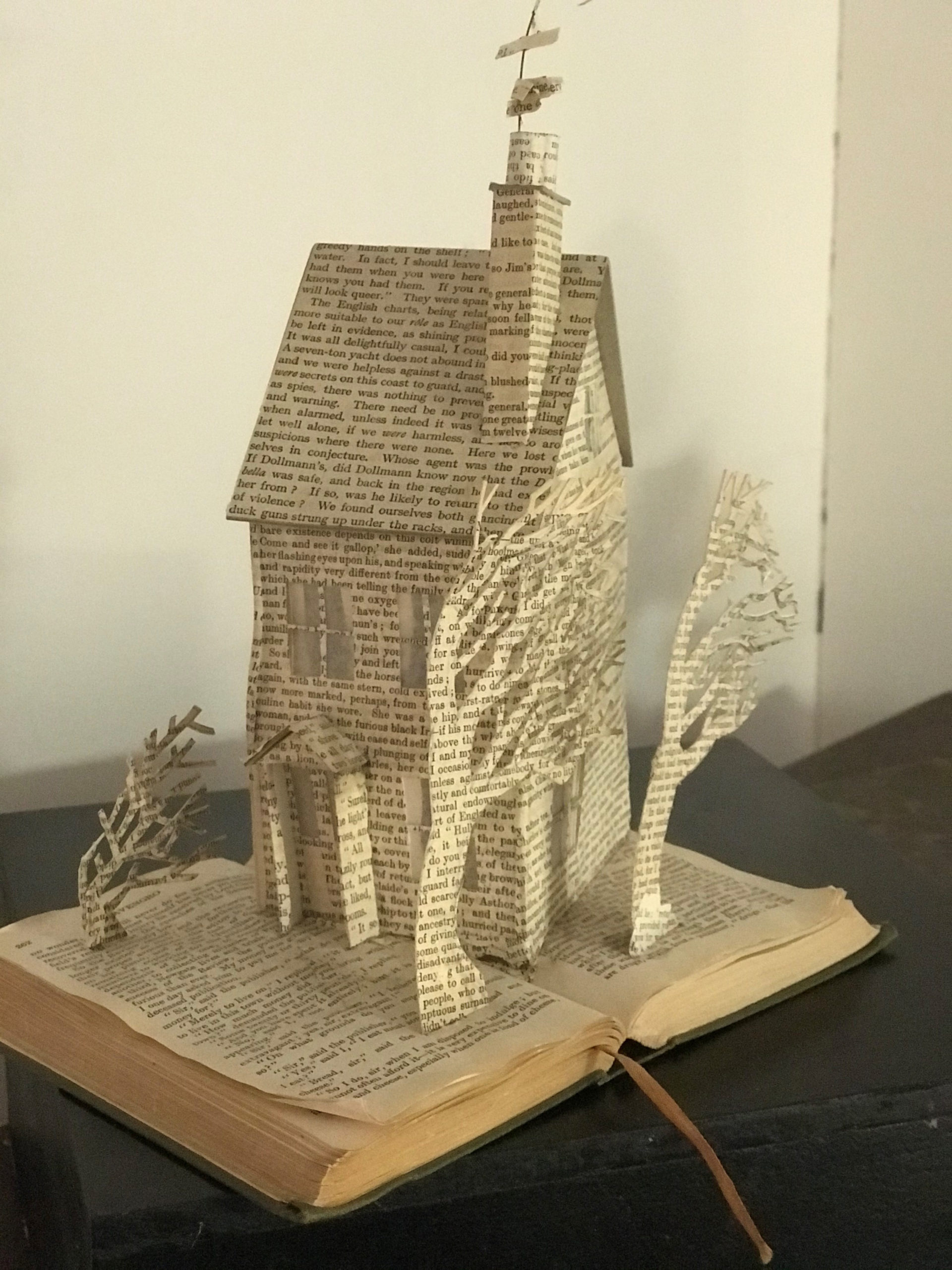 Modern colour photo of an open printed book with a 3D paper house and trees also made from printed book sheets
