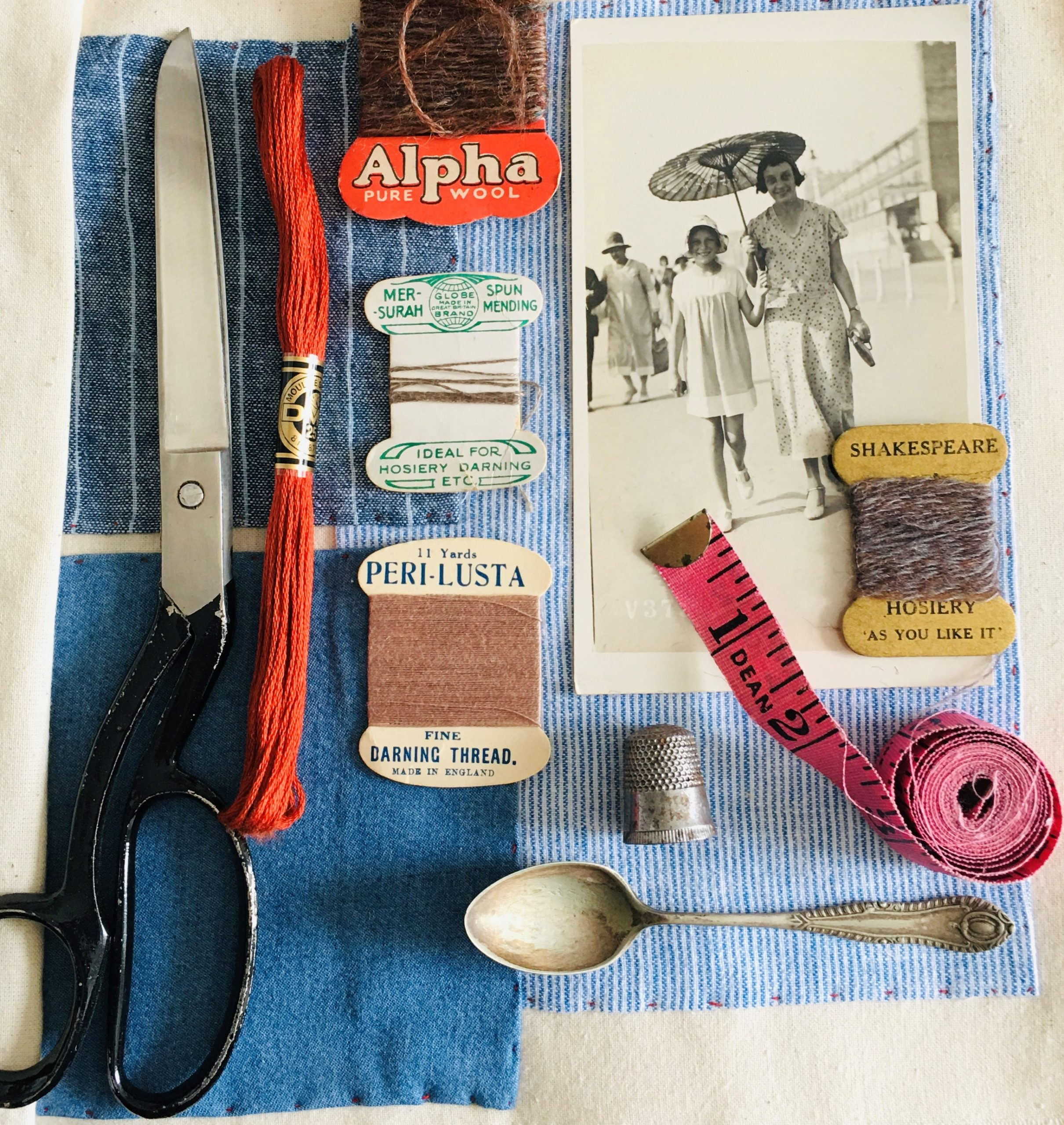 Modern colour photo flatlay of various vintage haberdashery materials including thread, thimble, vintage teaspoon, as well as vintage photos and a pair of scissors