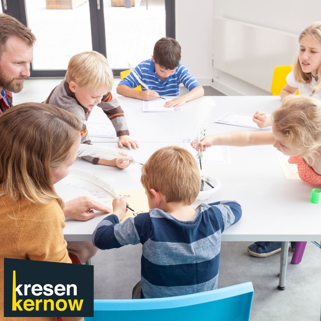 Modern colour photo of children at a table drawing with parents watching