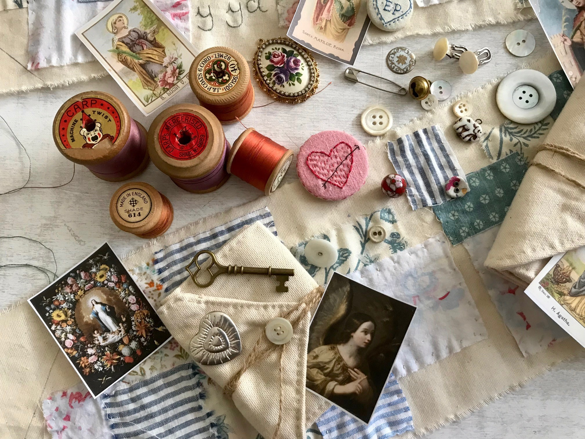 mondern colour photograph of a flatlay showing a variety of haberdashery items such as vintage cotton reels, buttons, fabric etc