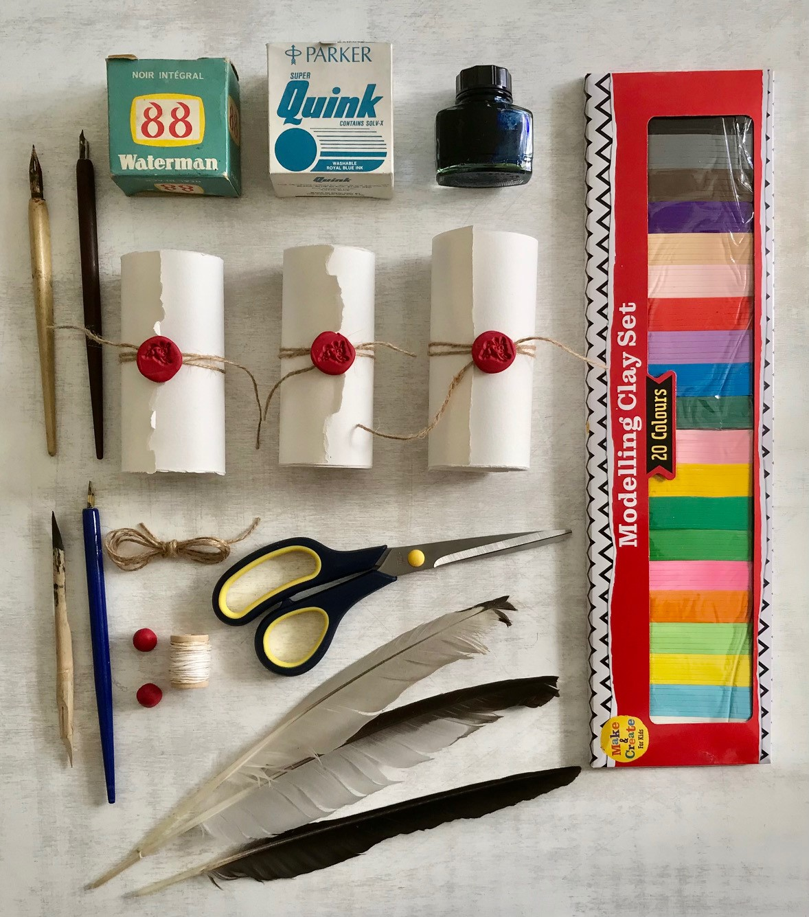 Colour photo showing ink, scrolls, quills and scissors.